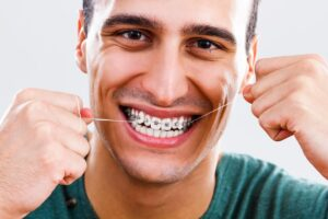 man flossing after learning what to know about braces